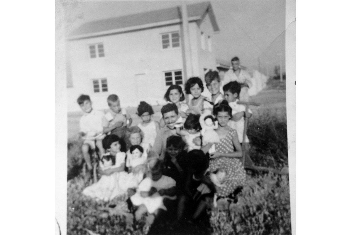 Manuel junto a sus hijos mayores: Irma, Leo y Patricia, junto a pequeños vecinos en un cumpleaños, alrededor de 1956. Población El Carmen, Santiago.