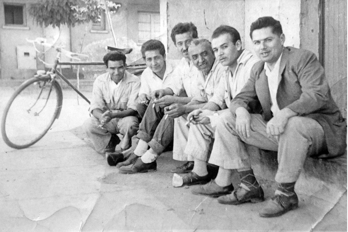 Manuel con sus amigos del trabajo de Industrias Hirmas, sentados fuera de la lavandería de la población. Manuel es el tercero de izq. a derecha. Santiago, alrededor de 1970.