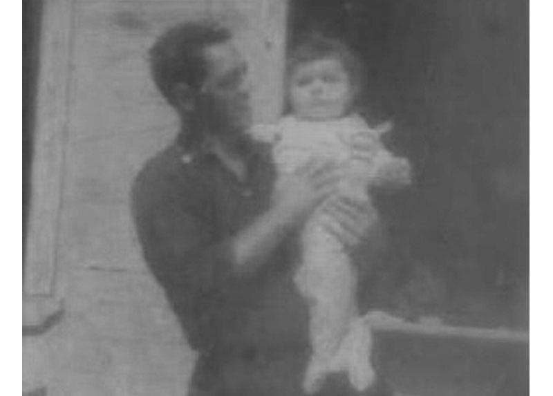 Humberto sostiene a su hijo Cristian. Están en el patio de la casa en que vivían, en la población Gómez Carreño de Iquique, diciembre de 1973.